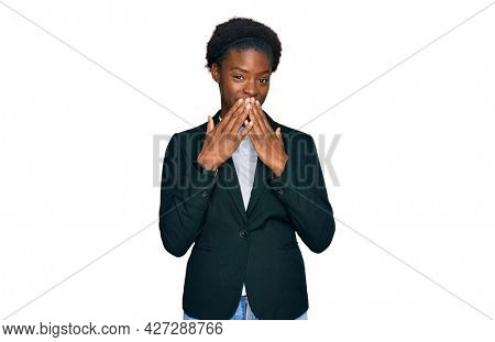 Young african american girl wearing business clothes laughing and embarrassed giggle covering mouth with hands, gossip and scandal concept