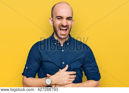 Young hispanic man wearing casual clothes smiling and laughing hard out loud because funny crazy joke with hands on body.