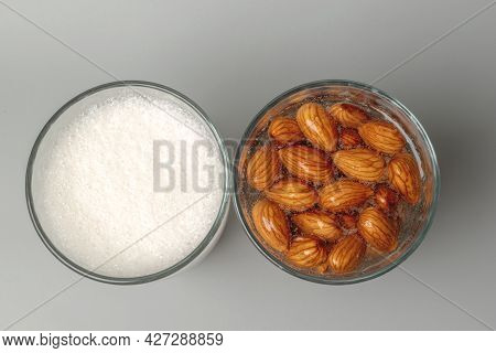 Top View Of Two Glasses With Soaked Almonds And With Almonds Milk. Showing Ingredients Needed To Pre