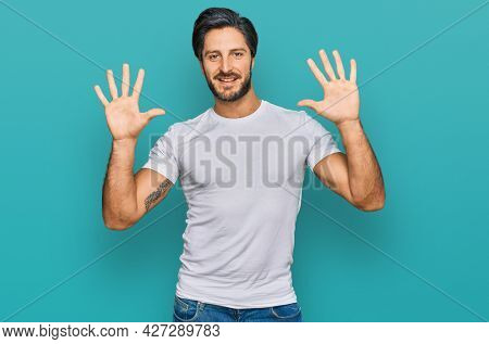 Young hispanic man wearing casual white t shirt showing and pointing up with fingers number ten while smiling confident and happy.