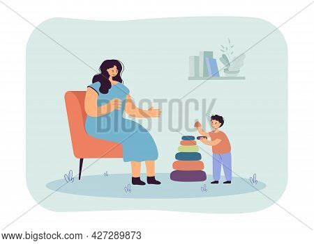 Mother Sitting On Chair, Helping Her Son Assemble Pyramid. Mom And Kid Playing And Spending Time Tog