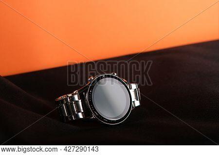 Smart Watch Lying On A Black Cloth. A Macro Photo Of A Silver Bracelet. Men's Wrist Accessory