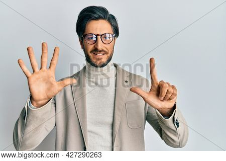Young hispanic man wearing business jacket and glasses showing and pointing up with fingers number seven while smiling confident and happy.