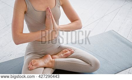 Motion past lady yoga practitioner in new beige tracksuit sitting in lotus position with namaste on mat in light studio closeup