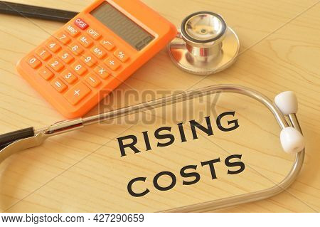 Calculator, Stethoscope On The Table With Phrase Rising Costs.