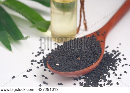 Black Cumin On Spoon With Oil In A Jar On Table.