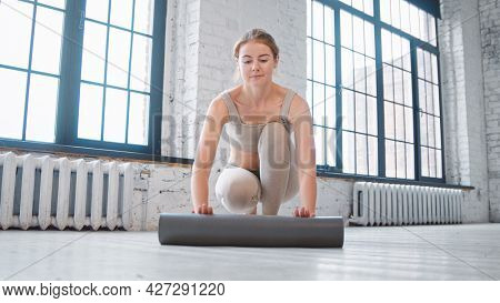 Smiling blonde woman with bun hairstyle in beige tracksuit unrolls mat to camera on floor near windows in spacious studio closeup