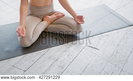 Peaceful woman with bare abdomen in tracksuit meditates in yoga lotus position sitting on mat in gym closeup space for design