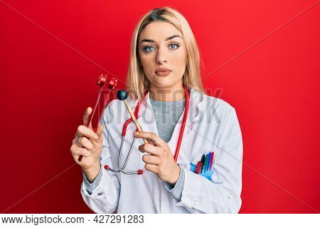 Young caucasian woman wearing doctor uniform holding tuning fork relaxed with serious expression on face. simple and natural looking at the camera.