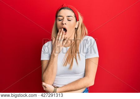 Young caucasian woman wearing casual white t shirt bored yawning tired covering mouth with hand. restless and sleepiness.
