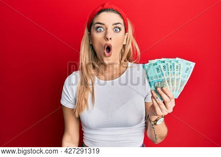 Young caucasian woman holding indian rupee banknotes scared and amazed with open mouth for surprise, disbelief face