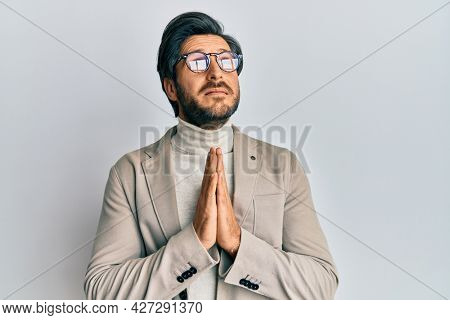 Young hispanic man wearing business jacket and glasses begging and praying with hands together with hope expression on face very emotional and worried. begging.