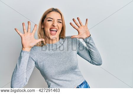 Young caucasian woman wearing casual clothes showing and pointing up with fingers number ten while smiling confident and happy.