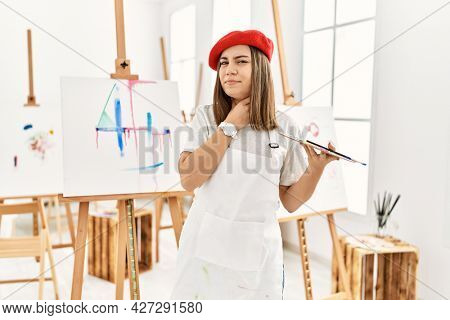 Young artist woman painting on a canvas at art studio touching painful neck, sore throat for flu, clod and infection