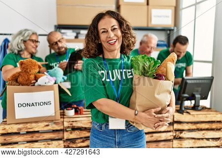 Group of middle age volunteers working at charity center. Woman smiling happy and holding paper bag with food to donate.