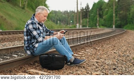 An Elderly Male Tourist Is Sitting On The Railway Tracks, Looking Through Information On The Phone A