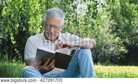 An Elderly White-haired Man With A Beard, Sitting Alone On The Grass In A Nature Park With A Book. A