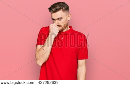 Young redhead man wearing casual clothes smelling something stinky and disgusting, intolerable smell, holding breath with fingers on nose. bad smell