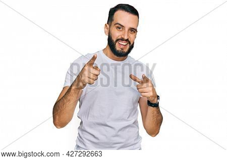 Young man with beard wearing casual white t shirt pointing fingers to camera with happy and funny face. good energy and vibes.