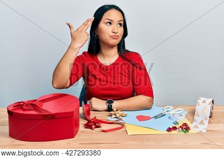 Beautiful hispanic woman with nose piercing doing handcraft creative decoration shooting and killing oneself pointing hand and fingers to head like gun, suicide gesture.