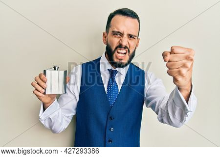Young man with beard drinking whiskey from flask annoyed and frustrated shouting with anger, yelling crazy with anger and hand raised