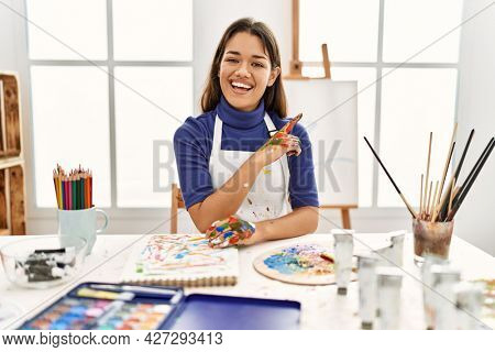 Young brunette woman at art studio with painted hands with a big smile on face, pointing with hand and finger to the side looking at the camera.