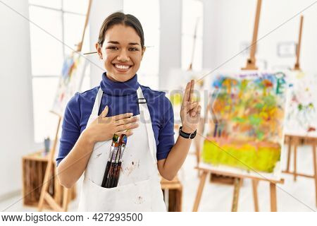 Young brunette woman at art studio smiling swearing with hand on chest and fingers up, making a loyalty promise oath