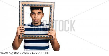Young african american man holding empty frame relaxed with serious expression on face. simple and natural looking at the camera.