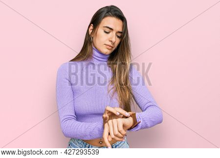 Young hispanic woman wearing casual clothes checking the time on wrist watch, relaxed and confident