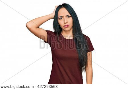 Young hispanic girl wearing casual t shirt confuse and wonder about question. uncertain with doubt, thinking with hand on head. pensive concept.
