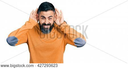 Hispanic man with beard wearing casual winter sweater trying to hear both hands on ear gesture, curious for gossip. hearing problem, deaf