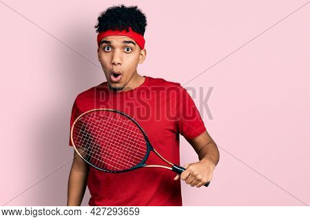 Young african american man wearing tennis player uniform scared and amazed with open mouth for surprise, disbelief face