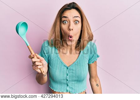 Young caucasian blonde woman holding silicone soup spoon scared and amazed with open mouth for surprise, disbelief face