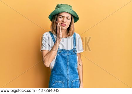 Young caucasian blonde woman wearing denim jumpsuit and hat with 90s style touching mouth with hand with painful expression because of toothache or dental illness on teeth. dentist