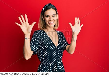 Young caucasian blonde woman wearing beautiful black and white dress showing and pointing up with fingers number ten while smiling confident and happy.