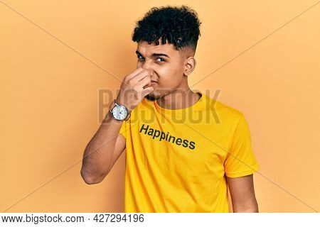 Young african american man wearing t shirt with happiness word message smelling something stinky and disgusting, intolerable smell, holding breath with fingers on nose. bad smell