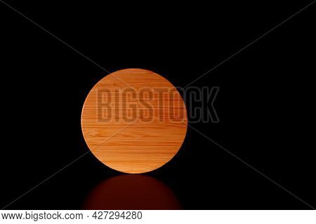 Close-up Round Textured Wooden Shape On Black Background With Reflection.low Key.copy Space For Text