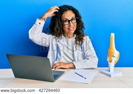 Beautiful middle age woman doctor at orthopedic clinic confuse and wonder about question. uncertain with doubt, thinking with hand on head. pensive concept.