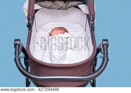 Baby Boy In A Carriage On A Blue Background. A Child In White Clothes In Only Diapers Is Lying In A