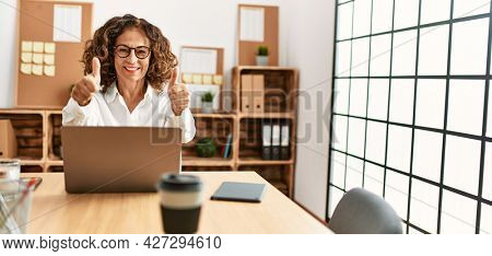 Middle age hispanic woman working at the office wearing glasses approving doing positive gesture with hand, thumbs up smiling and happy for success. winner gesture.