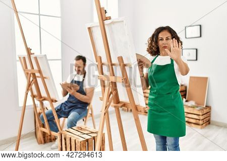Hispanic middle age woman and mature man at art studio with open hand doing stop sign with serious and confident expression, defense gesture