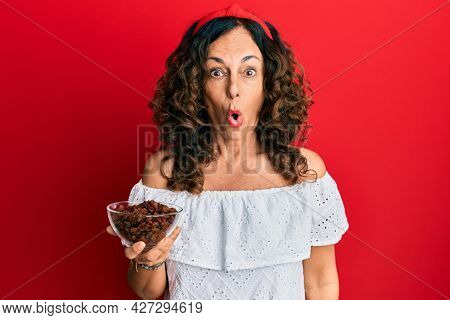 Middle age hispanic woman holding bowl with raisins scared and amazed with open mouth for surprise, disbelief face