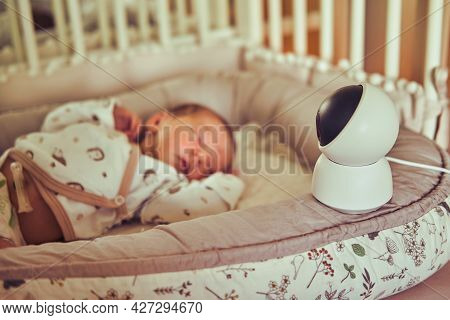 A Home Surveillance Camera Looks At The Crib With A Sleeping Newborn Baby