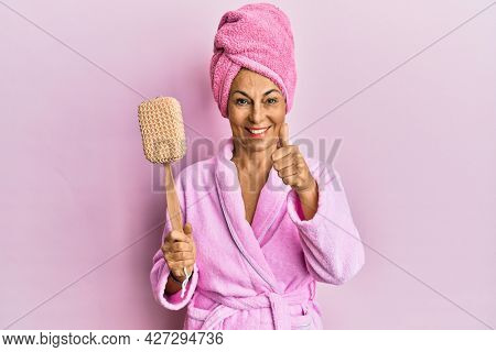 Middle age hispanic woman wearing bathrobe holding sponge smiling happy and positive, thumb up doing excellent and approval sign