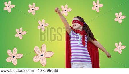 Composition of flowers over girl in superhero costume. girl power, positive female strength and independence concept digitally generated image.