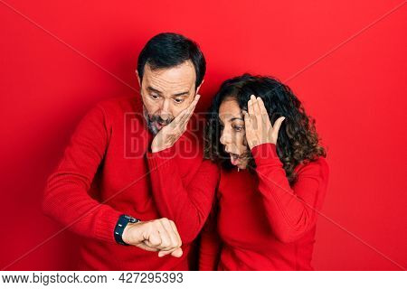 Middle age couple of hispanic woman and man hugging and standing together looking at the watch time worried, afraid of getting late