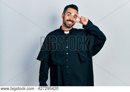 Handsome hispanic man with beard wearing catholic priest robe doing peace symbol with fingers over face, smiling cheerful showing victory