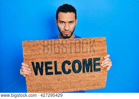 Hispanic man with beard holding welcome doormat skeptic and nervous, frowning upset because of problem. negative person.