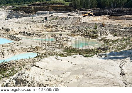 Digging Excavator On A Quarry With Kaolin Clay, Light Sand And Blue Water, Beautiful Landscape, Indu