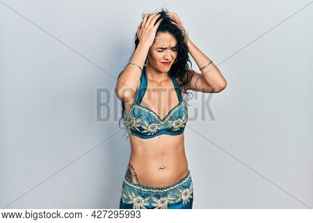 Young woman wearing bindi and traditional belly dance clothes suffering from headache desperate and stressed because pain and migraine. hands on head.
